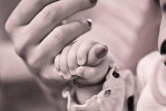 Baby greift Hand